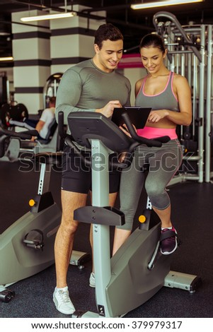 Attractive young woman working out on an exercise bike in gym, muscular trainer consulting her. Both smiling