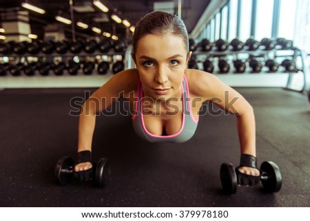 Attractive young woman working out with dumbbells and doing push ups in gym - stock photo