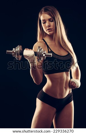 attractive young woman working out with dumbbells - bikini fitness girl with healthy lifestyle and perfect body - stock photo