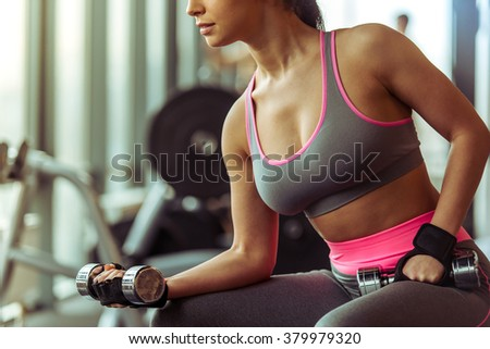 Attractive young woman working out with dumbbells in gym, cropped - stock photo