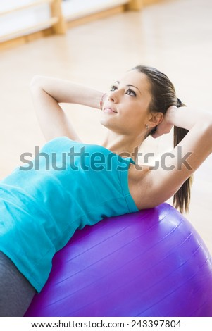 Attractive young woman working out with fitness ball in the gym, pilates exercise. - stock photo