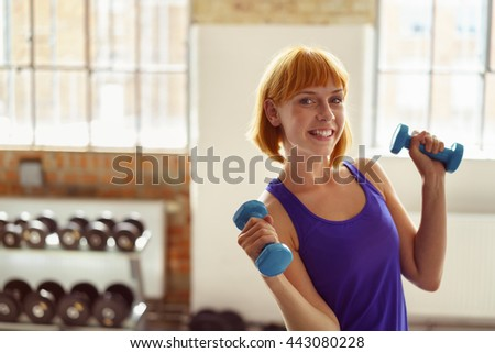 Attractive young woman working out with weights standing in a gym grinning happily at the camera as she holds to dumbbells in her hands - stock photo
