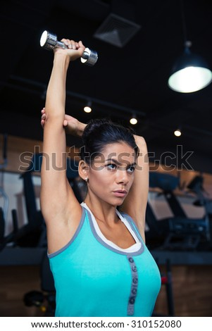 Attractive young woman workout with dumbbell in gym - stock photo