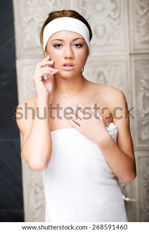 Attractive young woman wrapped in towel in bathroom. - stock photo
