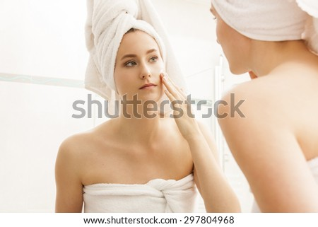 Attractive Young Woman Wrapped with Bath Towels, Applying Cream on her Face After a Shower at the Bathroom. - stock photo