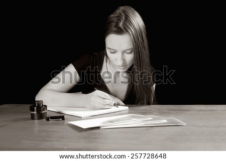 Attractive young woman writing a letter at an old table, monochrome photo - stock photo