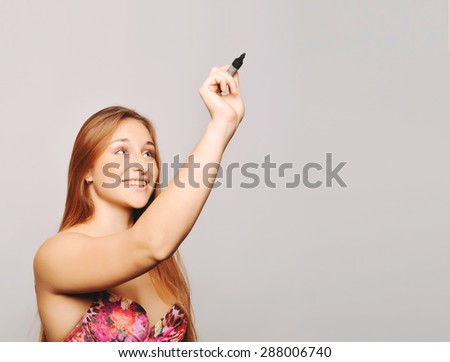 Attractive young woman writing with marker, isolated over plain background. Copyspace. - stock photo
