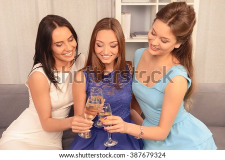 Attractive young women clinking with glasses of champagne