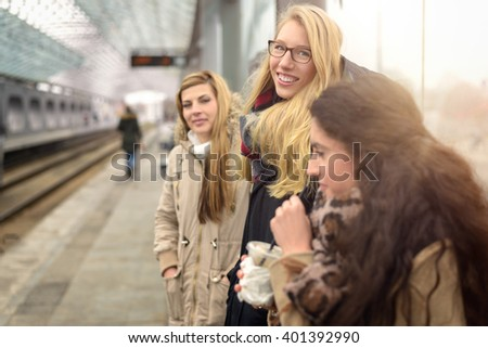 Attractive young women of various heights waiting for train on modern commuter station platform outdoors - stock photo