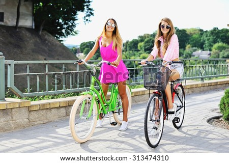 Attractive young women on a bicycles - outdoor fashion portrait