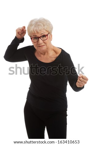 Attractvie old woman with closed fists. Isolated on white.
