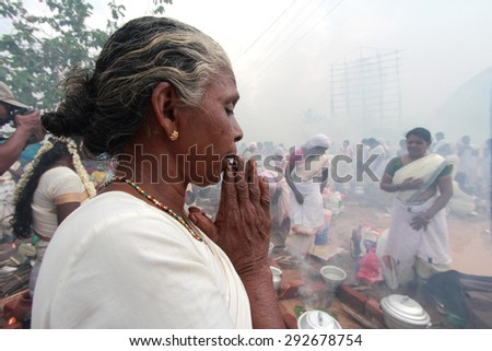 ATTUKAL, INDIA - MAR 7: An unidentified devotee prays during the 'Attukal Pongala' on March 7, 2012 in Attukal,Kerala,India.The event is considered as the largest gathering of women in the world. - stock photo