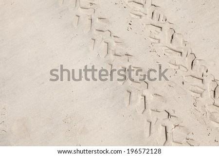ATV tracks on the white sand beach. Closeup photo - stock photo