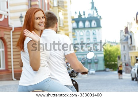Au revoir and good bye. Back view of a happy couple riding away on a retro scooter, while red-haired girl turning back and waving and smiling - stock photo
