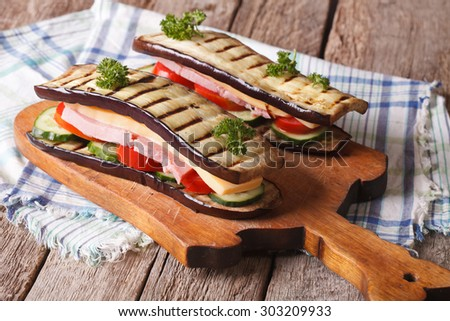 Aubergine sandwiches with fresh vegetables, ham and cheese on the table. horizontal