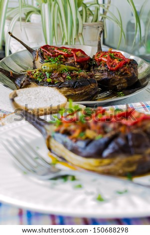 Aubergine stuffed with vegetables in white plate - stock photo