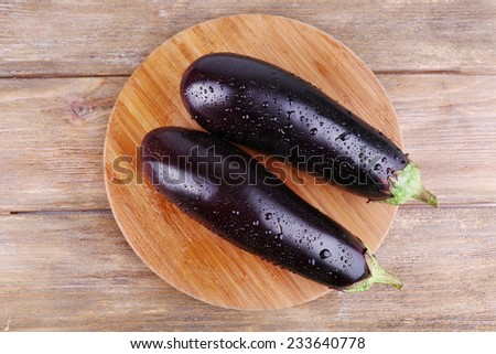 Aubergines on round cutting board on wooden background - stock photo