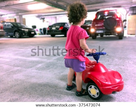 AUCKLAND - FEB 10 2016:Little girl (Naomi Ben-Ari age 2) play with a toy car in parking lot. In the U.S. at least  50 children are being backed over by vehicles EVERY week. - stock photo
