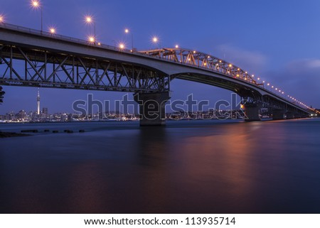 Auckland Harbour Bridge/ a New Zealand icon and landmark, shot at night with the auckland city lights in the background - stock photo