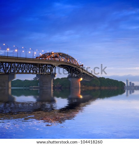 Auckland Harbour Bridge with its lights on, just before dawn. - stock photo