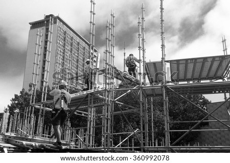 AUCKLAND -  JAN 09 2016: Scaffold builders at work.OSHA statistics report that about 28% of the scaffold accidents that occur are the result of construction deficiencies. - stock photo