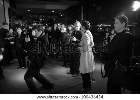 AUCKLAND - JUNE 5: Paparazzi and media gather outside the opening night party at the new Louis Vuitton flagship store in Queen Street on June 5, 2008 in Auckland, New Zealand. - stock photo