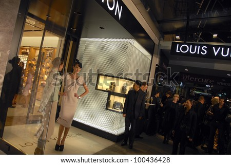AUCKLAND - JUNE 5: Two models pose for photographers on opening night of Louis Vuitton's new flagship store in Queen Street on June 5, 2008 in Auckland, New Zealand. - stock photo