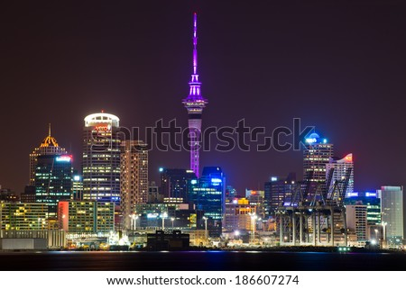 AUCKLAND, NEW ZEALAND - APRIL 10: The Sky Tower glowing royal purple to celebrate the Royal tour of New Zealand on April 10, 2014 in Auckland, New Zealand. - stock photo