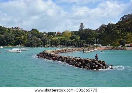 Auckland, New Zealand - October 04, 2016: Man and boy fishing from the Breakwater at Waiheke Island, Auckland.
