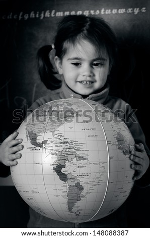 AUCKLAND, NZ - JULY 26:A girl (Talya Ben Ari age 3) holds a globe during geography lesson on July 26 2013. The oldest known world maps date back to ancient Babylon from the 9th century BC.