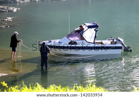 AUCKLAND, NZ - JUNE 02:Peopelmooring a motor boat on June 02 2013.There is about  450-500,000 of boats in NZ, 10,000 of them are personal watercraft. - stock photo