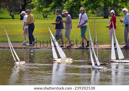 AUCKLAND, NZL - DEC 21 2014:People racing remote controlled sailing wooden yachts in a pond.The racing is governed by the same Racing Rules of Sailing that are used for full-sized crewed sailing boats - stock photo