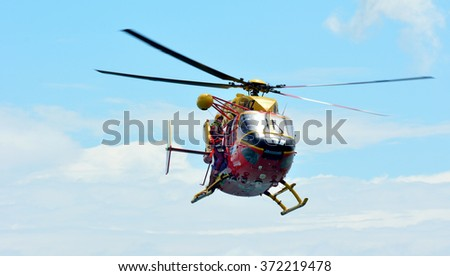 AUCKLAND,  NZL - JAN 30 2016:Westpac Rescue Helicopter crew in rescue mission.The crew are trained and equipped to operate day and night to medical transfers medevacs to rescue searches and airlifts. - stock photo