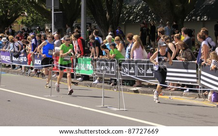 AUCKLAND- OCT. 30: Unidentified participants in the Adidas Auckland marathon run sprint to the finish line on Sunday Oct. 30,2011 in  Auckland, New Zealand - stock photo