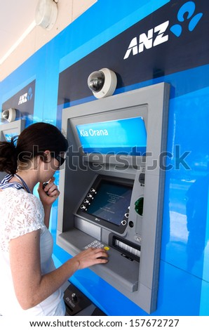 AUCKLAND - SEP 21:Young woman (30's) use an ANZ Bank ATM Machine on Sep 21 2013.It's the largest bank in NZ and the most sustainable bank globally according to the 2008 Dow Jones Sustainability Index