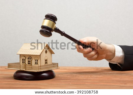 Auction, Real Estate concept. Hand with judge gavel and house model - stock photo