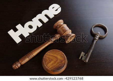 Auctioneers or Judges Hammer or Gavel with White Home or House Sign On Black Wooden Background, Trial Or Auction Concept - stock photo