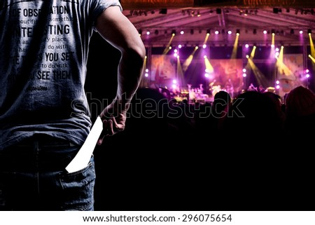 Audience presenting tickets or admission passes watch a concert - stock photo