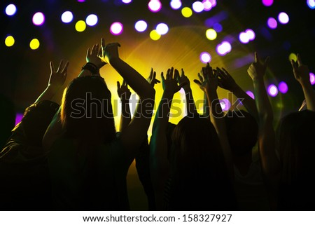 Audience watching a rock show with hands in the air