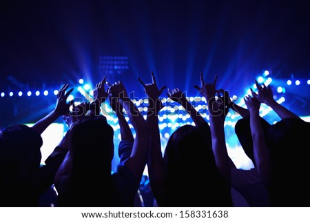 Audience watching rock show with hands in the air