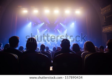 Audience watching the scene with the artists. - stock photo