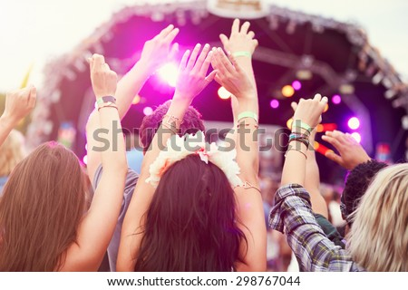 Audience with hands in the air at a music festival - stock photo