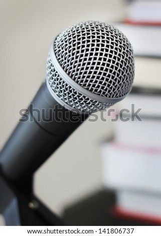 Audio books narration recording vocal microphone against background of books