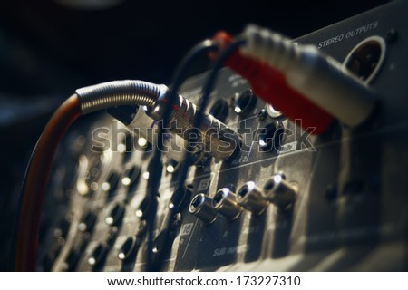audio cable coming into analogue sound mixer in recording studio, indoor blurred shot with particular focus on center - stock photo