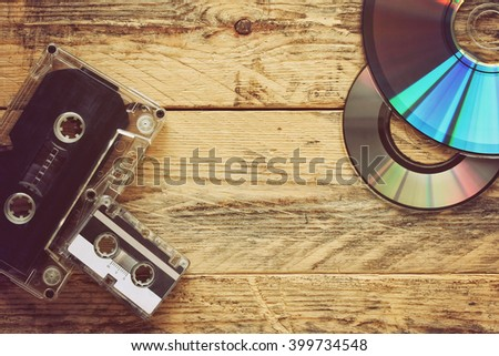 audio cassettes and CD discs on a wooden table - stock photo