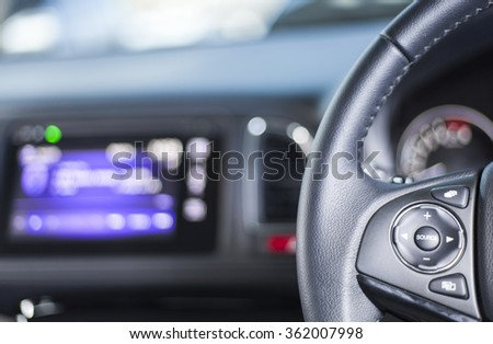 Audio control buttons on the steering wheel of a modern car - stock photo