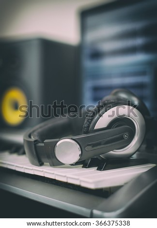 Audio earphones. Home recording studio with professional monitors and midi keyboard. - stock photo