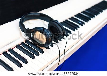 audio earphones on piano keyboards. - stock photo