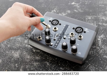 Audio interface for recording or mixing - sound/audio card, and woman's hand holding amplifier - stock photo