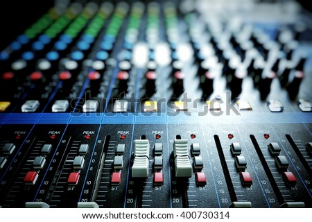 Audio mixer console with light shading in control room - stock photo